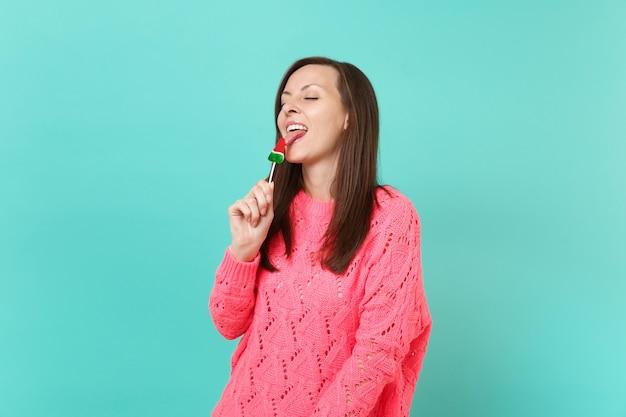 Bela jovem de suéter rosa de malha com olhos fechados, segurando na mão, lambendo o pirulito de melancia isolado no fundo da parede azul, retrato de estúdio. conceito de estilo de vida de pessoas. simule o espaço da cópia.