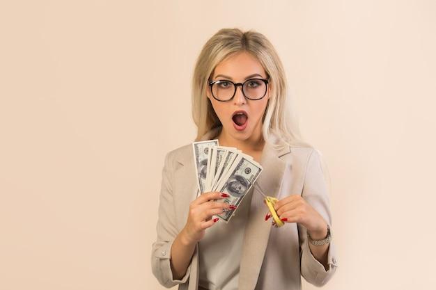 Bela jovem de terno bege corta dólares com uma tesoura