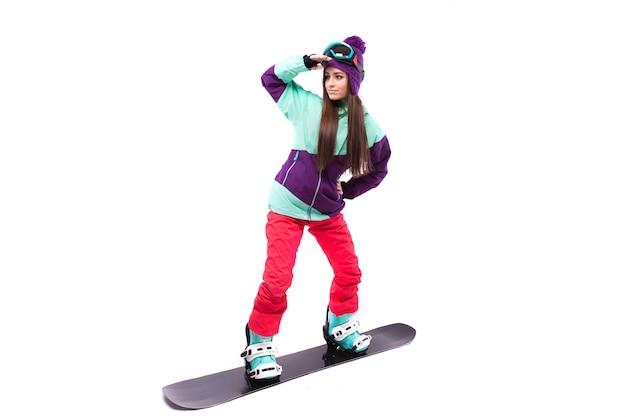 Bela jovem de terno de esqui roxo monta snowboard preto