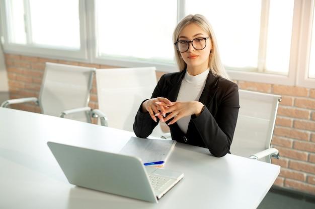 Bela jovem de terno no escritório à mesa com um laptop