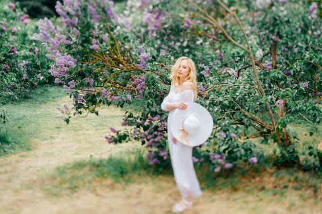 Bela jovem de vestido branco elegante e chapéu posando no parque florescendo.