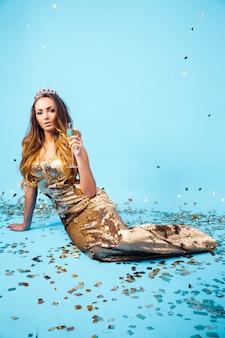 Bela jovem de vestido dourado com champanhe