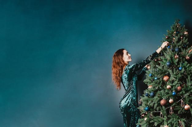 Bela jovem decorando a árvore de natal