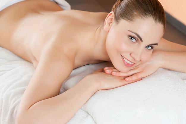 Bela jovem deitada e relaxando no centro de spa de beleza