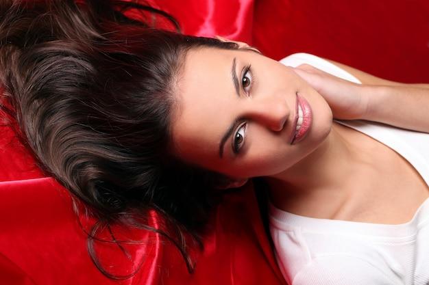 Bela jovem deitada em seda vermelha, vista superior