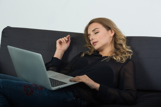 Bela jovem deitada em um sofá preto com um laptop