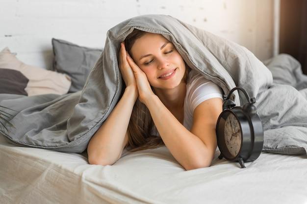 Bela jovem deitada na cama, debaixo de um cobertor