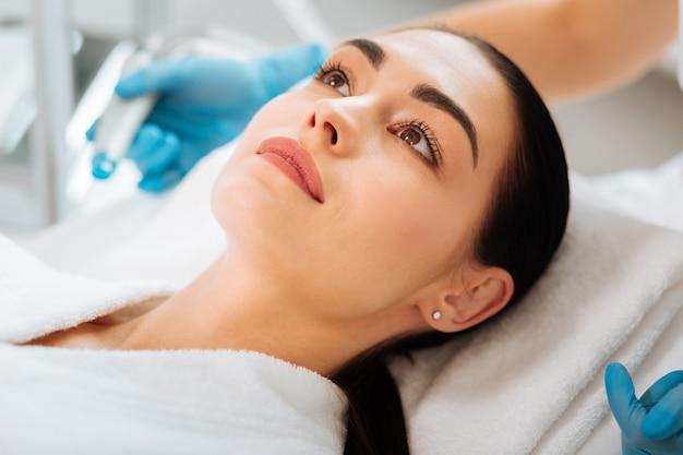 Bela jovem deitada na cama médica durante um procedimento de beleza