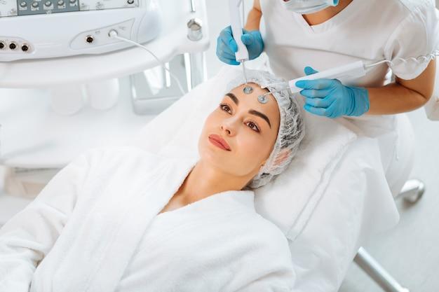Bela jovem deitada na cama médica durante um procedimento de microcorrente