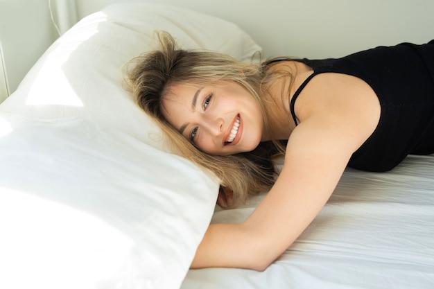 Bela jovem deitada na cama no quarto