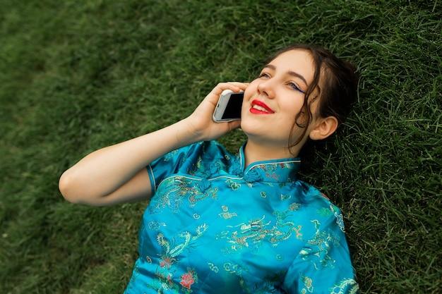 Bela jovem deitada na grama verde com o celular