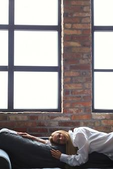 Bela jovem deitada no sofá em um apartamento moderno