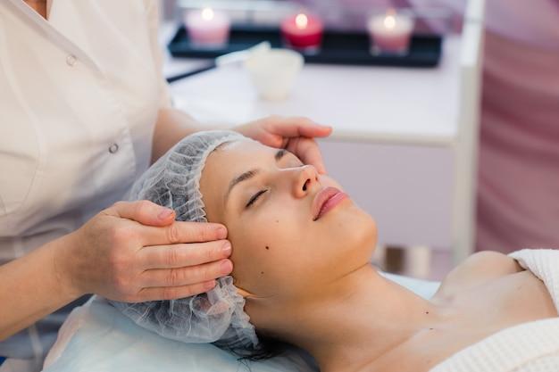 Bela jovem deitado relaxado em um salão de spa e recebendo massagem facial