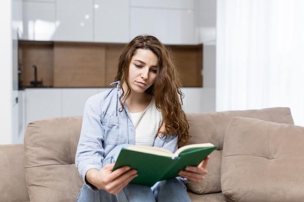 Bela jovem descansando em casa sentada no sofá e lendo um livro interessante