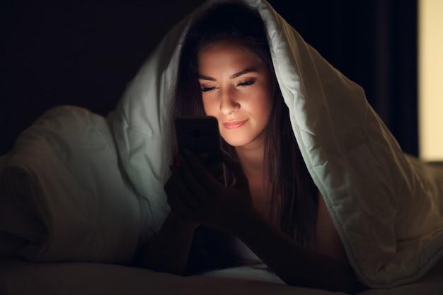 Bela jovem descansando na cama com smartphone