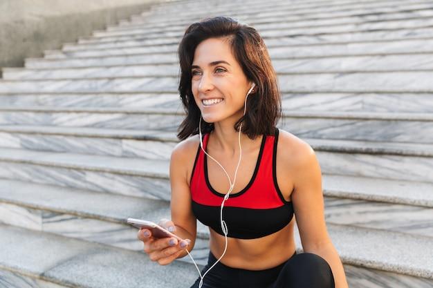 Bela jovem desportista segurando um telefone celular, ouvindo música com fones de ouvido, bebendo água