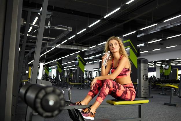 Bela jovem desportiva sentado na máquina de exercício no ginásio
