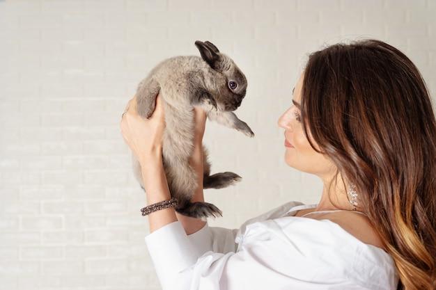 Bela jovem detém um coelho cinzento fofo e fofo
