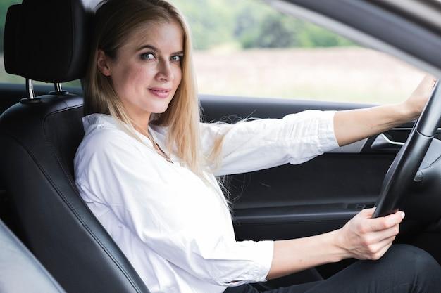 Bela jovem dirigindo plano médio