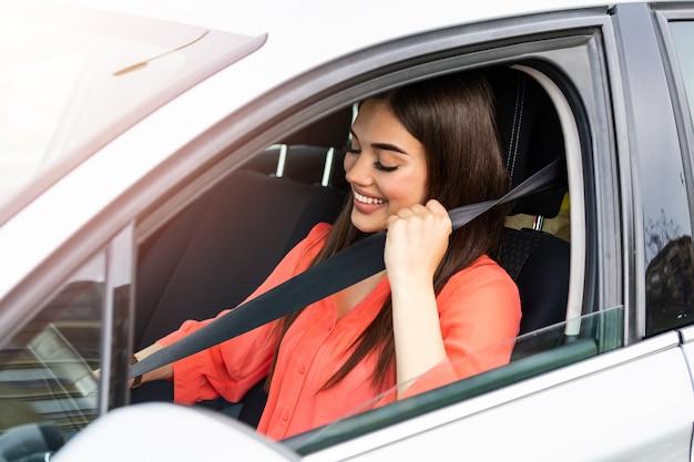 Bela jovem dirigindo seu carro novo. cinto de segurança de fixação feminina no carro
