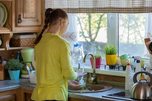 Bela jovem dona de casa lavando pratos enquanto limpa a casa