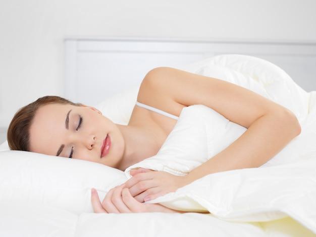 Bela jovem dormindo deitada de lado no quarto