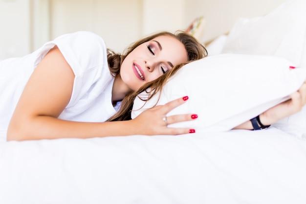 Bela jovem dormindo em sua cama e relaxando pela manhã