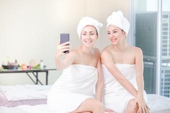 Bela jovem e amigos relaxante salão de spa com a tomada de selfi no spa resort
