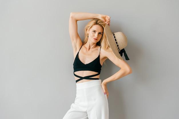 Bela jovem e elegante modelo loira posando em estúdio
