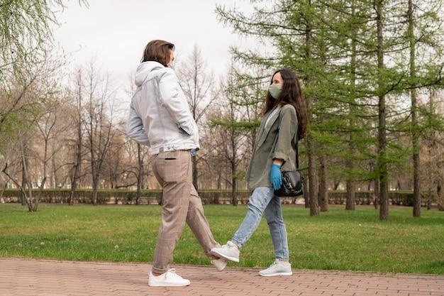 Bela jovem e o namorado com máscaras e roupa casual esticando as pernas enquanto se divertem