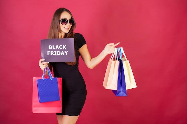 Bela jovem elegantemente vestida de preto com sacos depois de fazer compras na sexta-feira negra
