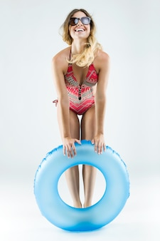 Bela jovem em biquíni brincando com flutuador. isolado no branco.