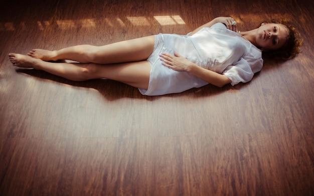 Bela jovem em camisola branca deitada no chão