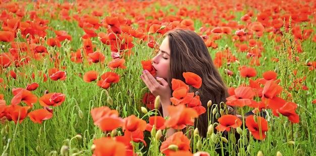 Bela jovem em campo de papoilas vermelhas.