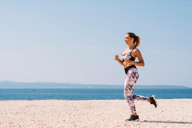 Bela jovem em fitness wear correndo na praia perto do mar