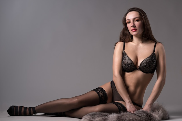 Bela jovem em lingerie e pele se senta no chão sobre um fundo cinza no estúdio.