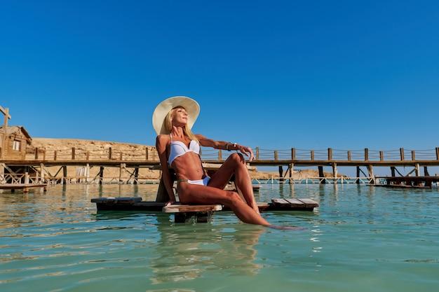 Bela jovem em maiô branco sentada no banco do cais do mar