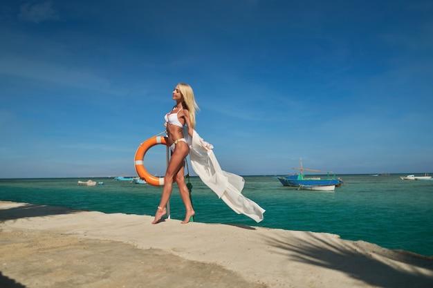 Bela jovem em pareo branco em pé no cais perto do mar