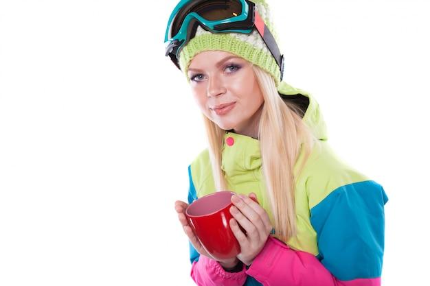 Bela jovem em roupa de esqui e óculos de esqui segurar copo vermelho