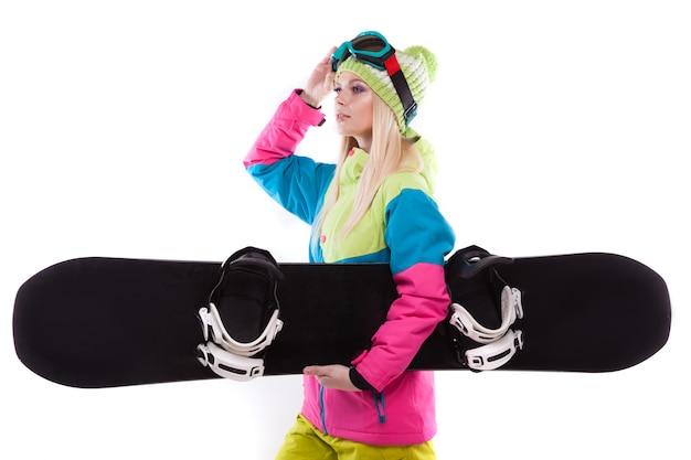 Bela jovem em roupa de esqui e óculos de esqui segurar snowboard