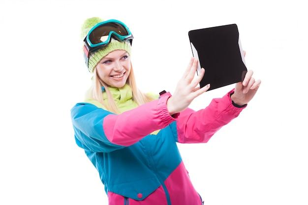Bela jovem em roupa de esqui e óculos de esqui segurar tablet