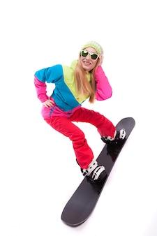 Bela jovem em roupa de esqui e óculos de sol passeio de snowboard
