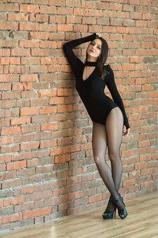 Bela jovem em roupa esportiva preta perto de uma parede de tijolos