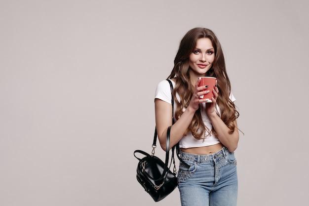 Bela jovem em roupas casuais com uma xícara de café para ir