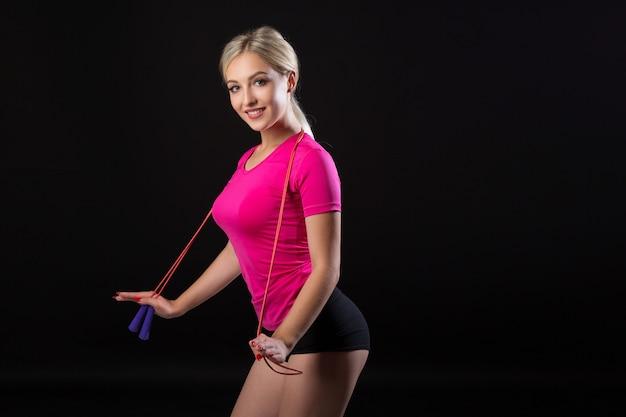 Bela jovem em roupas esportivas com uma corda de pular no preto
