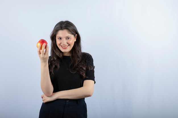 Bela jovem em top preto segurando maçã fresca.