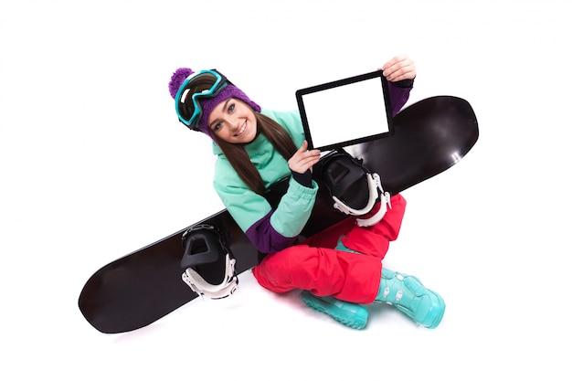 Bela jovem em traje de esqui roxo localização de pernas cruzadas, mostrar tablet vazio