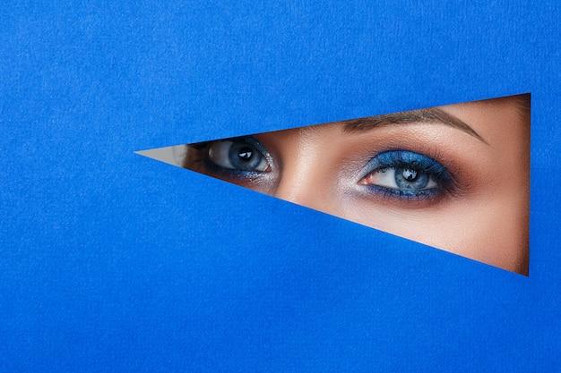 Bela jovem em um buraco no papel azul, bela maquiagem brilhante,