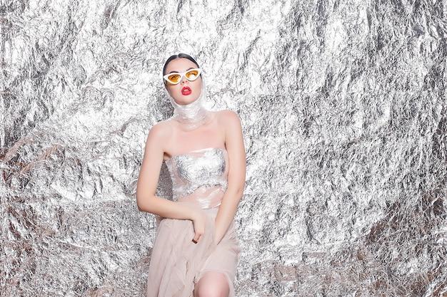 Bela jovem em um fundo prateado. mulher artística com estilo com maquiagem de fantasia. criatividade. retrato da moda de uma jovem bonita e elegante com uma festa brilhante