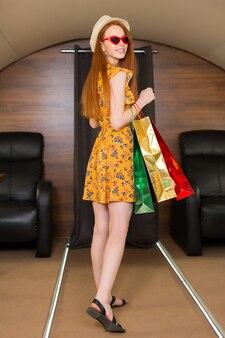 Bela jovem em um vestido amarelo em um jato particular com pacotes